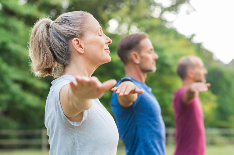 group-people-doing-yoga-breathing-exercises-nature-men-woman