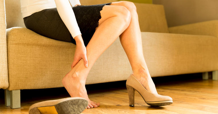 Woman in heels holding her leg in pain