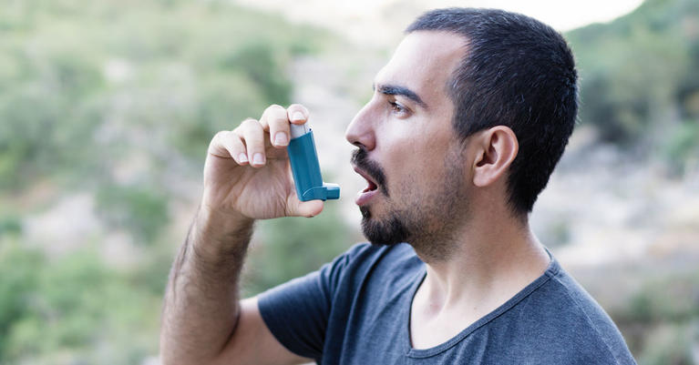 Man using his inhaler outside.