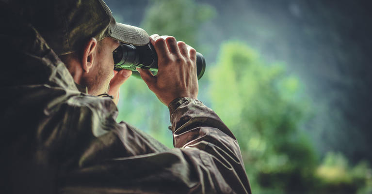 Man with binoculars in the woods