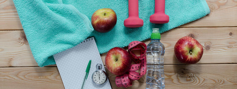 Exercise equipment, apples, timer and a workout towel.