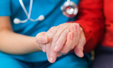 Patient and care-taker holding hands